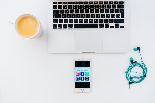 Laptop, fones de ouvido, café e telefone com aplicativos populares