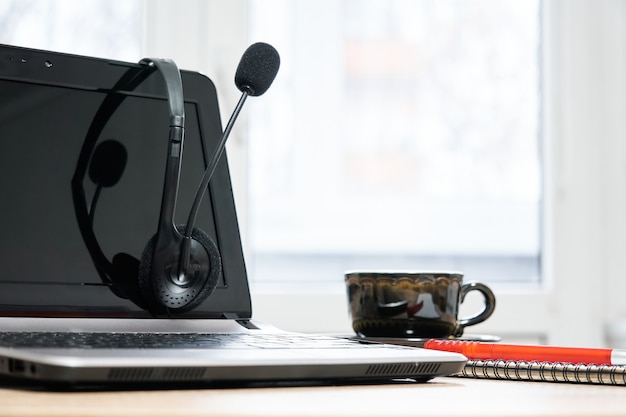 Laptop, fones de ouvido com microfone, notebook com caneta e xícara de café em cima da mesa close up