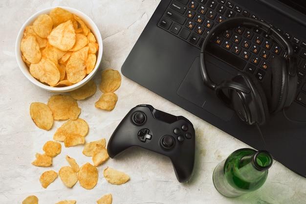 Laptop, gamepad, fones de ouvido, batatas fritas, garrafa de cerveja em uma superfície de pedra clara. conceito de jogos de computador e lazer