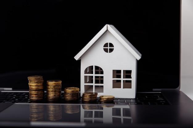 Laptop modelo de casa e conceito de hipoteca closeup de moedas