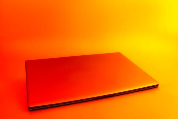Laptop moderno fino com tela branca mockup definida contra luz criativa vermelha brilhante.
