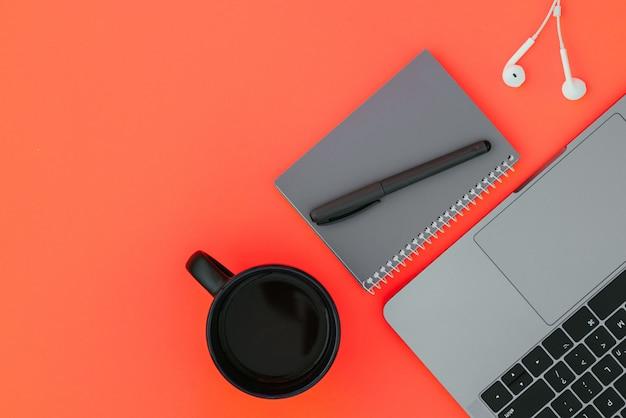 Laptop moderno, fones de ouvido brancos, caderno cinza com uma caneta e uma xícara de café na superfície vermelha