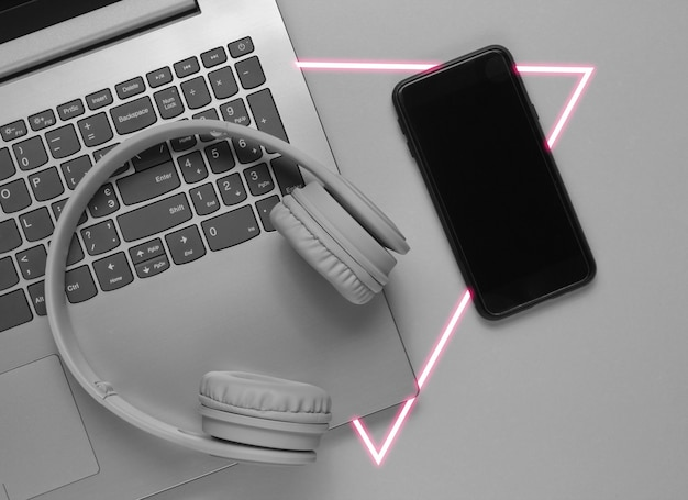 Laptop moderno, fones de ouvido sem fio, smartphone.