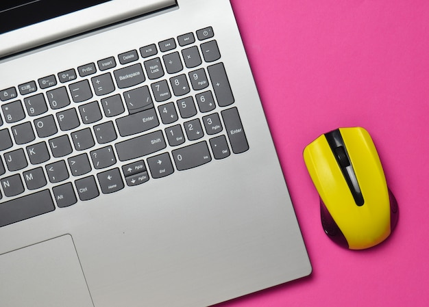 Laptop moderno, mouse sem fio em um fundo rosa, minimalismo, vista superior, plana leigos