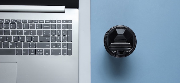 Laptop moderno, xícara de café sobre fundo azul cinza. vista do topo. plano de escritório
