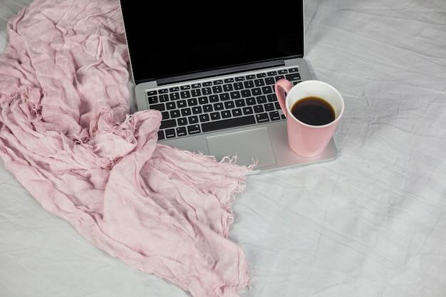 Laptop na cama com uma xícara de café