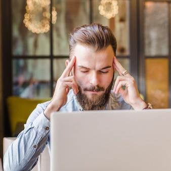 Laptop na frente do jovem estressado