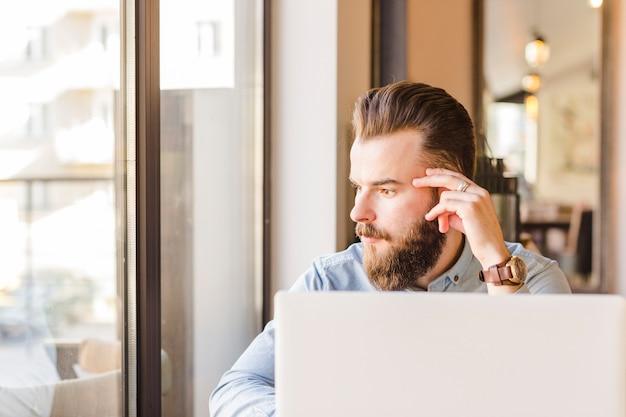 Laptop na frente do jovem sentado no café