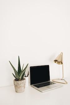 Laptop na mesa branca com lâmpada dourada e planta aloe. espaço de trabalho mínimo para escritório em casa com modelo de maquete