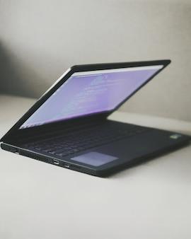 Laptop na mesa com o código dos programadores. trabalho em casa, trabalho remoto