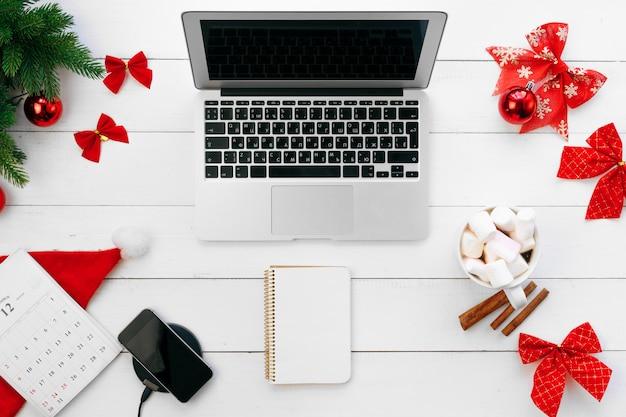 Laptop na mesa de madeira branca, cercada com decorações de natal vermelhas, vista superior