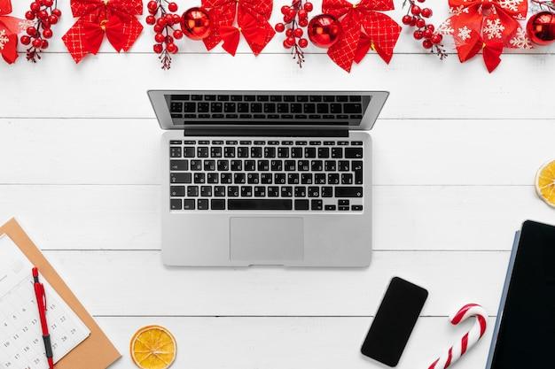 Laptop na mesa de madeira branca, cercada com decorações de natal vermelhas