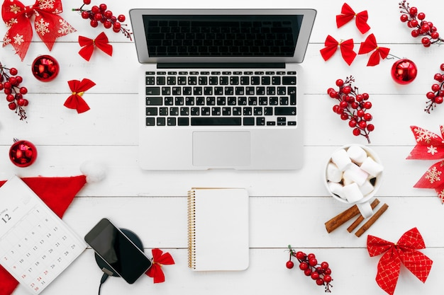 Laptop na mesa de madeira branca rodeada de decorações de natal vermelhas, vista superior