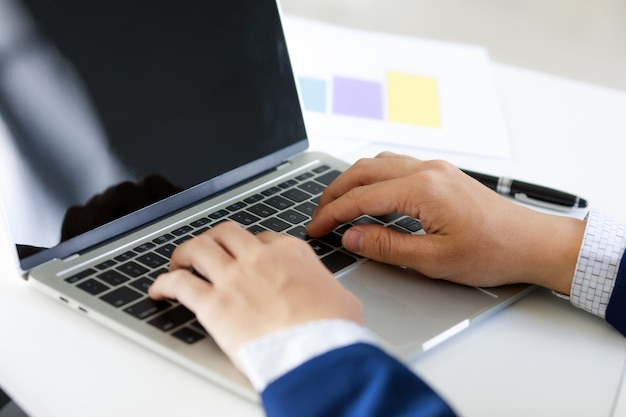 Laptop na mesa do escritório com a mão do homem de negócios na digitação de terno azul marinho. conceito de local de trabalho de estilo legal.