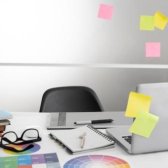 Laptop na mesa do escritório com cadeira e notebook