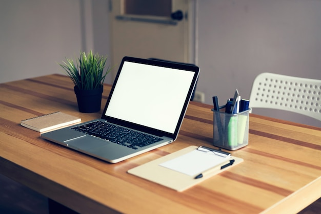 Laptop na mesa no fundo de sala de escritório, para montagem de exibição de gráficos.