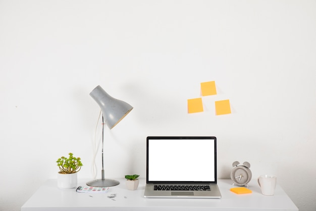 Laptop na mesa perto de decorações e notas autoadesivas