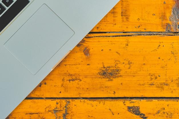 Laptop no fundo da tabela do escritório. vista superior do caderno na mesa de madeira.