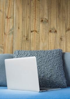 Laptop no sofá em frente a parede de madeira