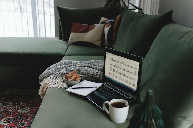 Laptop no sofá verde. trabalho a partir de casa. loft ou interior moderno.