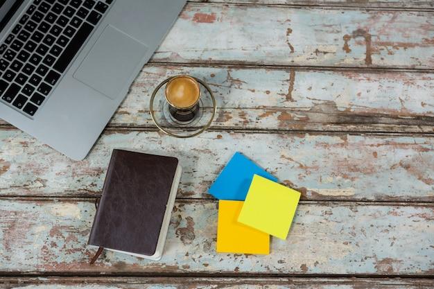 Laptop, notas autoadesivas e diário com uma xícara de café