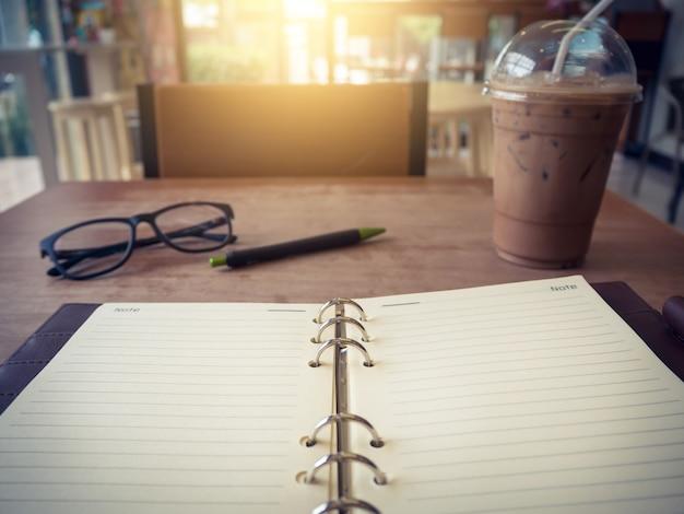 Laptop (notebook) com copo de café gelado e o bloco de notas com a caneta na mesa de madeira velha.
