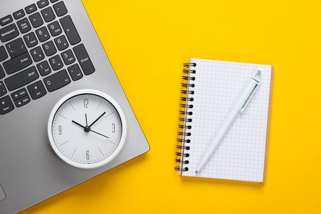 Laptop, notebook e despertador em fundo amarelo. o tempo está fugindo. o conceito de prazos urgentes no trabalho e compromissos.