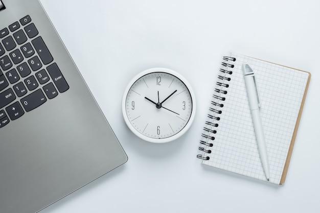 Laptop, notebook e despertador em fundo branco. o conceito de prazos urgentes no trabalho e compromissos. vista do topo