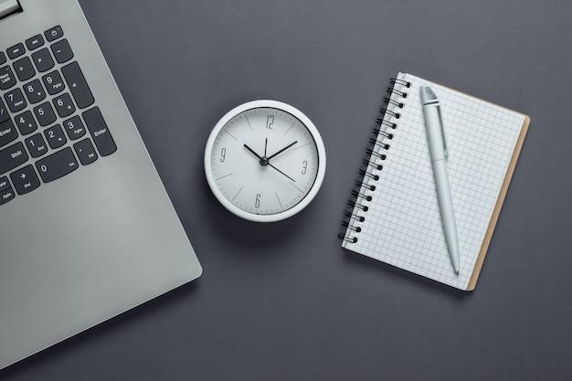 Laptop, notebook e despertador na superfície cinza. o tempo está fugindo. o conceito de prazos urgentes no trabalho e compromissos. vista do topo