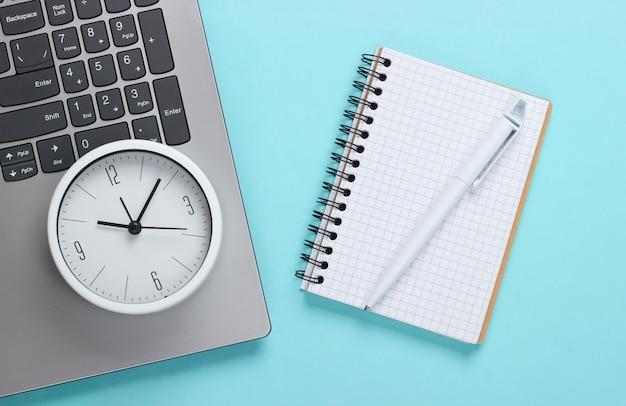 Laptop, notebook e despertador sobre fundo azul. o tempo está fugindo. o conceito de prazos urgentes no trabalho e compromissos.