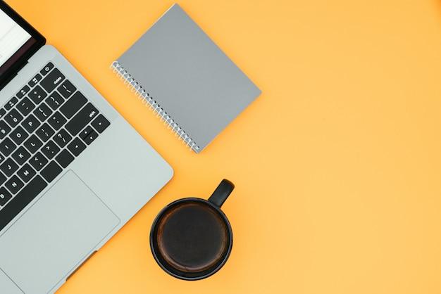 Laptop, notebook e xícara com café em uma superfície laranja, vista superior, local de trabalho