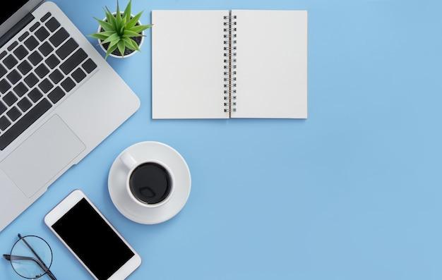 Laptop, notebook, smartphone e uma mão pegando uma xícara de café em um fundo azul claro