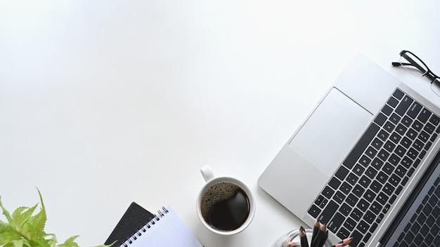 Laptop, notebooks e xícara de café sobre fundo branco.