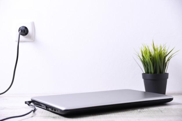 Laptop, o computador está carregando de uma tomada de 220 volts em uma mesa perto da parede. energia, acumulação. brincar