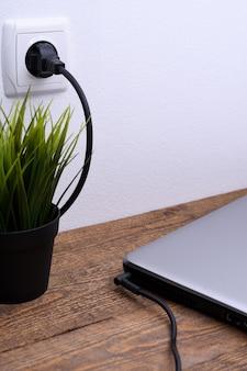 Laptop, o computador está carregando de uma tomada de 220 volts em uma mesa perto da parede. energia, acumulação.