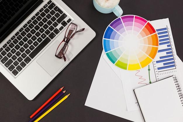 Laptop, óculos, lápis de cor, tabela de esquemas de cores, xícara de café, gráfico de negócios e diário