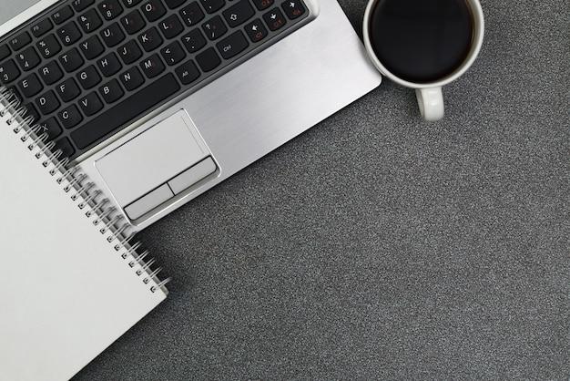 Laptop ou caderno, nota e xícara de café na tabela de funcionamento com opinião superior do espaço da cópia.