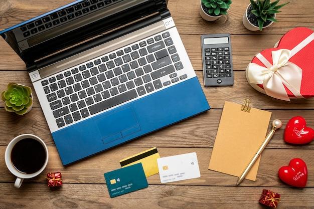 Laptop para escolhe o presente, faz compras, cartão de débito, xícara de café, dois corações na mesa de madeira