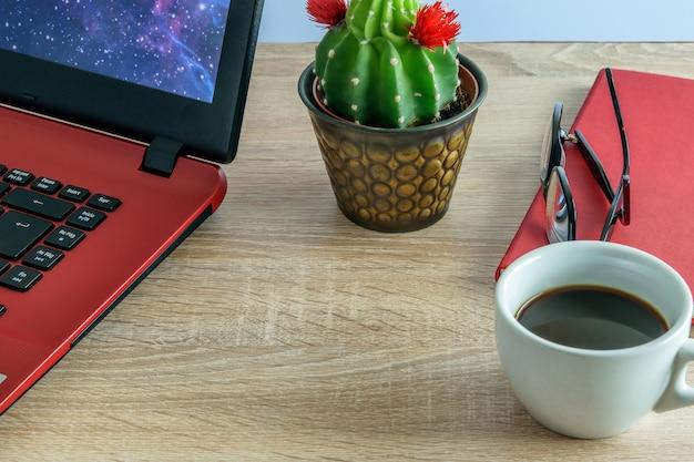 Laptop para trabalhar, uma xícara de café, cacto, óculos e caderno para fazer anotações.