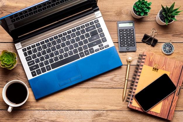 Laptop para trabalho a distância, faz compras, xícara de café, calculadora, smartphone, suculentas na