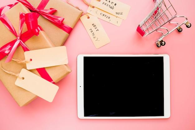 Laptop perto de carrinho de compras e caixas de presentes