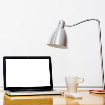 Laptop perto de copo, lâmpada e mouse de computador