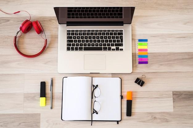 Laptop perto de óculos, bloco de notas e fones de ouvido no chão