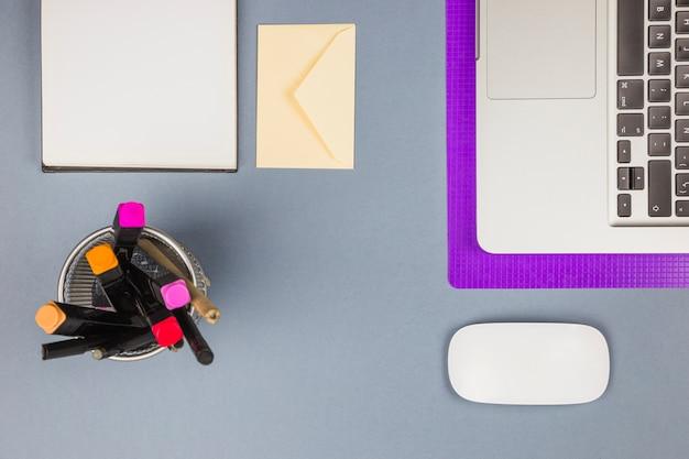 Laptop perto de papel, copo com canetas de feltro, carta e mouse de computador