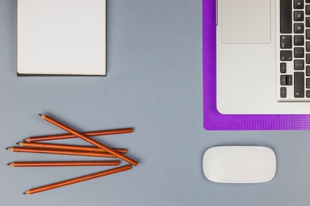 Laptop perto de papel, lápis e mouse de computador