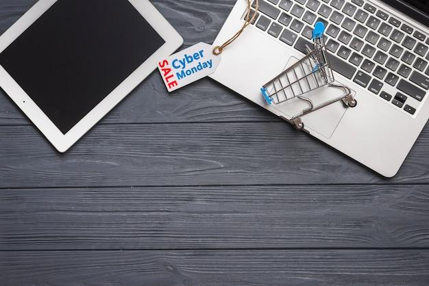 Laptop perto de tag, tablet e carrinho de supermercado
