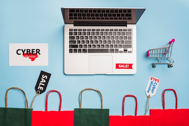 Laptop perto de tags, carrinho de compras e pacotes