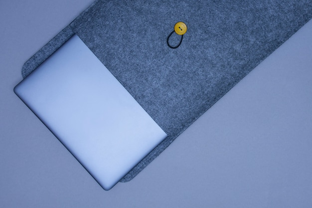 Laptop prata fechado em uma caixa protetora em um fundo cinza. vista do topo.