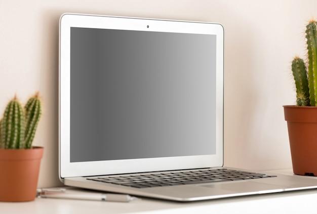 Laptop prateado compacto com tela preta desligada, sentado na prateleira com dois cactos em potes marrons. visto em close-up do ângulo