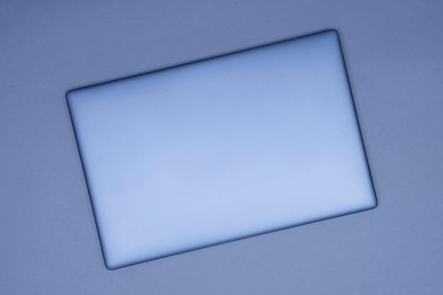 Laptop prateado fechado em um fundo cinza. vista do topo.